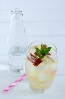 Cocktail de maçã com hortelã sobre fundo branco de madeira.
