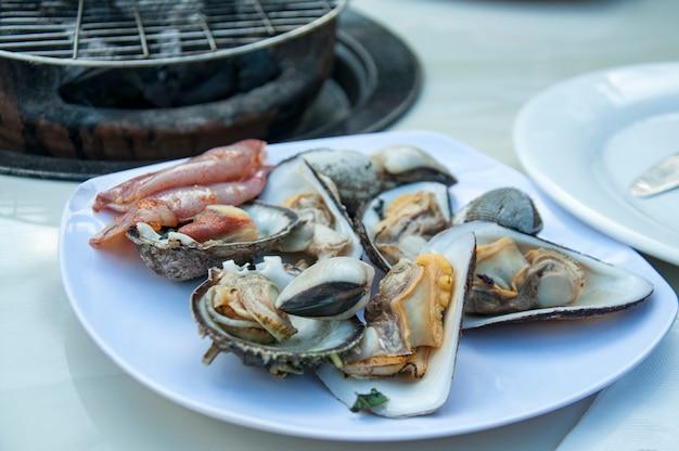 Cocktail de marisco. ostras, conchas do mar, mexilhões em uma placa antes de grelhar.