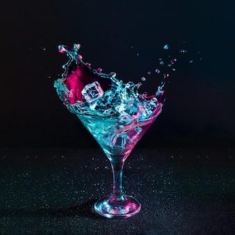Cocktail de martini splash com cubos de gelo nas cores rosa e azul iridescente neon
