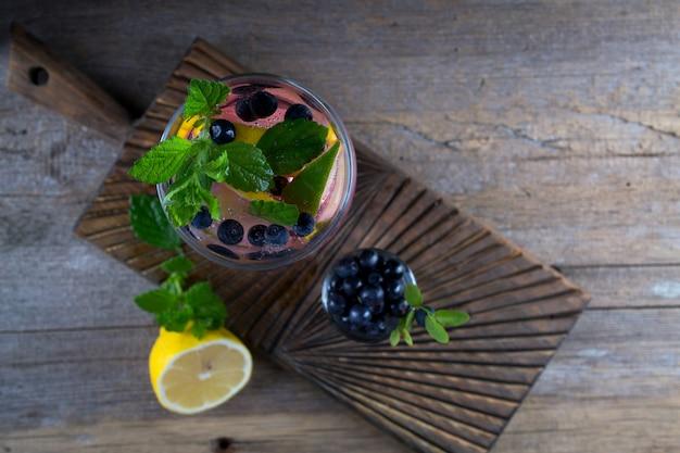 Cocktail de mirtilo - mojito com bagas frescas de limão, limão, gelo e hortelã no fundo de madeira velho vista superior, copie o espaço