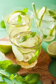 Cocktail de mojito fresco e ingredientes sobre a mesa verde