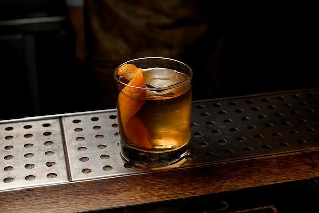 Cocktail de ouro no copo com um grande cubo de gelo estampado e raspas de laranja