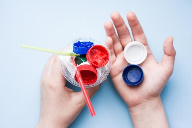 Cocktail de perigo do saco de plástico e tampas de garrafa com palha colorida nas mãos de crianças. conceito de poluição ambiental com plástico.