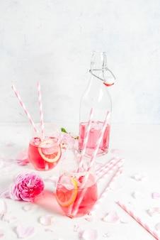 Cocktail de rosa rosa claro, com vinho rosé, pétalas de chá e limão em uma mesa de concreto de pedra branca.