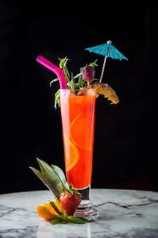 Cocktail de suco de laranja com acessórios coloridos.