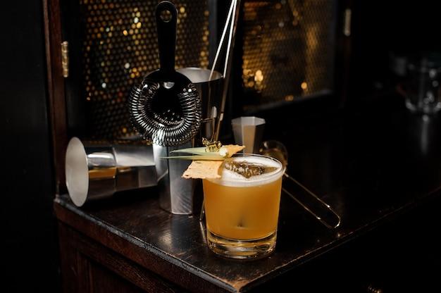 Cocktail de verão alcoólico amarelo fresco e azedo, com decoração e utensílios dispostos na mesa do bar