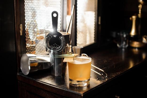 Cocktail de verão alcoólico decorado amarelo fresco e azedo e utensílios dispostos na mesa de bar
