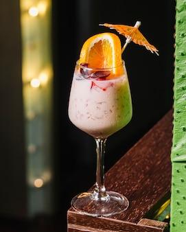Cocktail de vista frontal com uma fatia de laranja e decoração