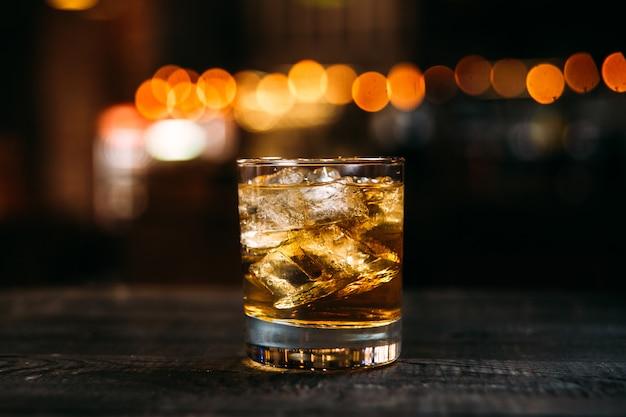Cocktail de whisky de refrigerante com cubos de gelo no copo à moda antiga em cima da mesa de madeira com fundo de luzes desfocadas bokeh