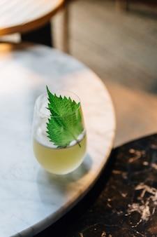 Cocktail de yuzu japonês com folhas de shiso (perilla verde) no vidro na tabela superior de mármore.