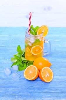 Cocktail do verão de mojito com hortelã, suco de lima, água de soda e gelo em uma tabela azul de madeira branca.