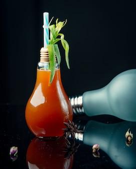 Cocktail em forma de lâmpada com folhas