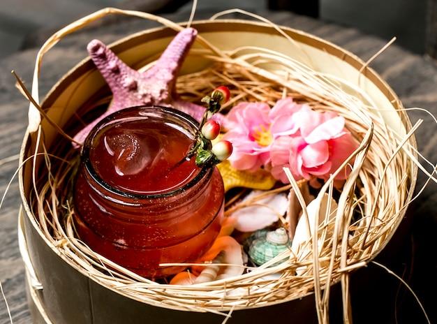 Cocktail em jarra colocada em caixa com conchas e estrelas do mar