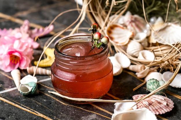 Cocktail em jarra colocada em torno de conchas e estrelas do mar
