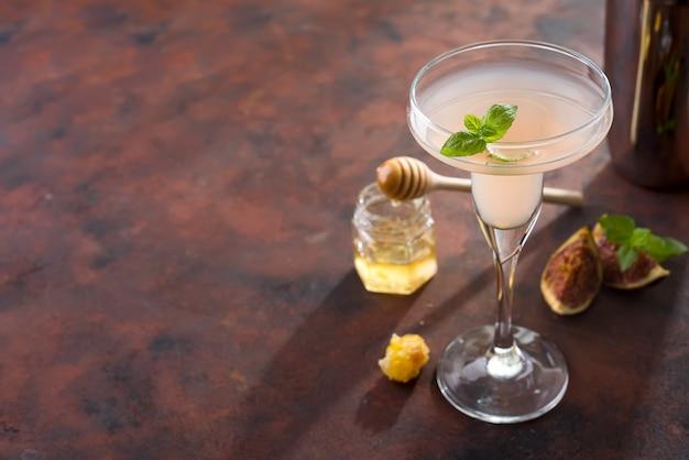 Cocktail exótico e figos, mel no fundo de pedra marrom, copie o espaço