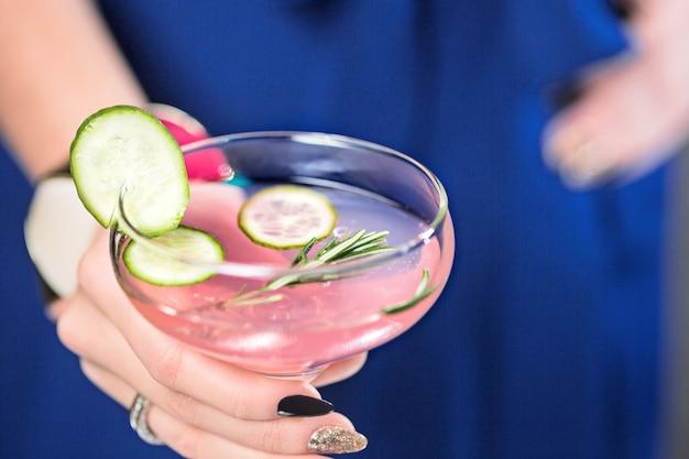 Cocktail exótico e mãos femininas