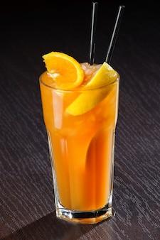 Cocktail exótico fresco com cubos de gelo e laranja em uma mesa de madeira