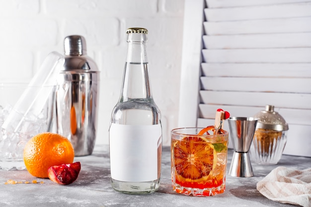 Cocktail fresco com laranja e limão no fundo de madeira branco,