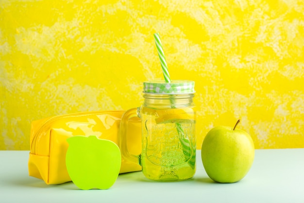 Cocktail fresco de vista frontal com maçã verde e caixa de caneta na superfície amarela