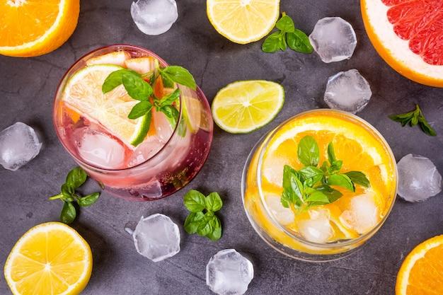 Cocktail frio cítrico em copos transparentes em fundo escuro
