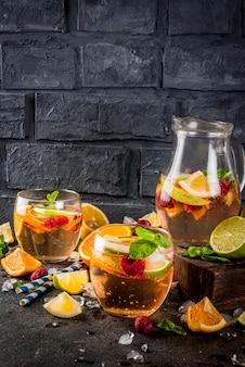 Cocktail frio de verão, sangria de frutas e bagas brancas com maçã, limão, laranja e framboesa