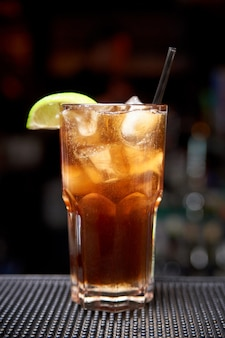 Cocktail frio em um fundo borrado escuro com bokeh.