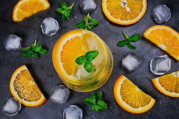 Cocktail frio laranja em vidro transparente em fundo escuro.