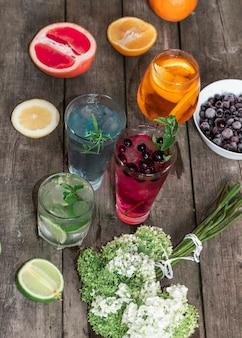 Cocktail gin tonic, mojito e aperol spritz com menta, gelo, limão, frutas, toranja e laranja no fundo de madeira.