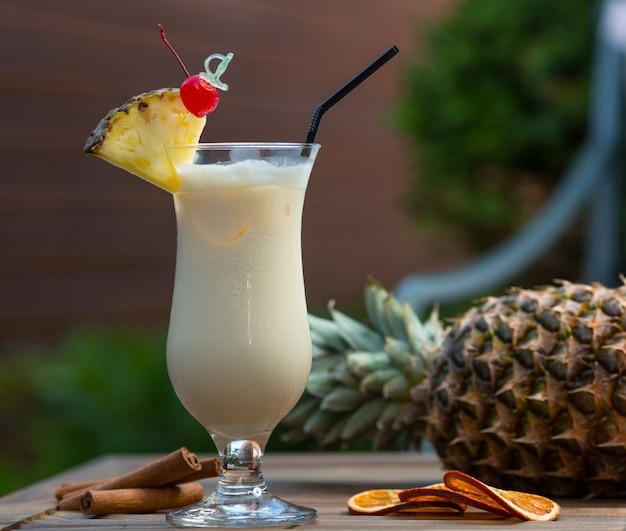 Cocktail leitoso no copo com uma fatia de abacaxi e uma cereja.