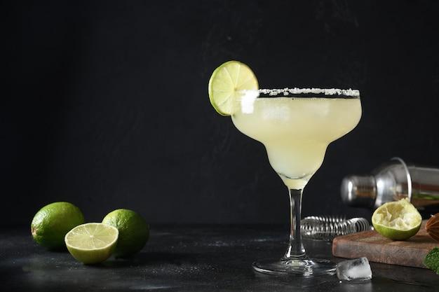 Cocktail margarita clássico com suco de limão e cubo de gelo em fundo preto escuro com espaço de cópia