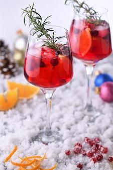 Cocktail margarita com cranberries, laranja e alecrim. um coquetel perfeito para uma festa de natal