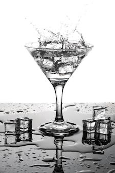 Cocktail martini com gelo em um copo. respingo e cubos de gelo.