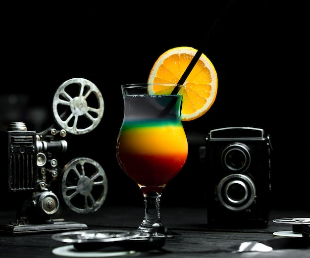 Cocktail multicolorido com gelo na mesa