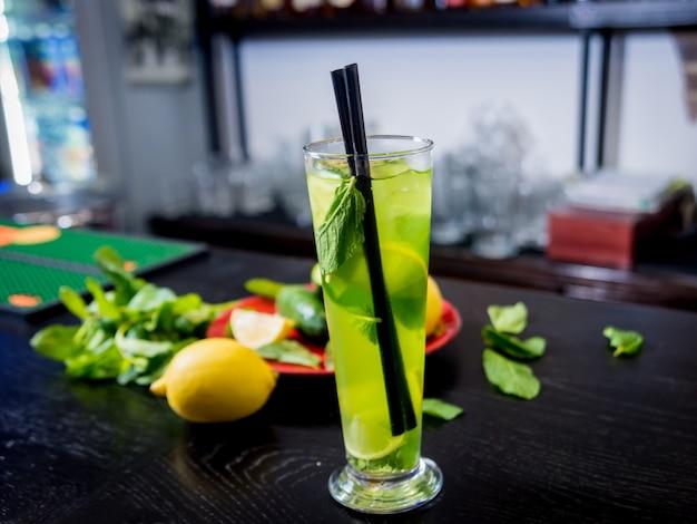 Cocktail não alcoólico com limão e hortelã no balcão de bar de madeira.