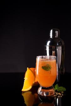 Cocktail negroni com laranja e uísque no backgorund preto de vidro