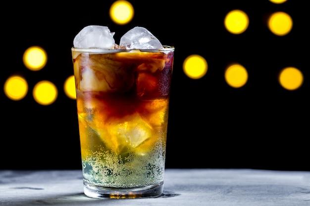 Cocktail refrescante com cubos de gelo e bolhas de refrigerante na superfície das luzes. café gelado. bebidas geladas e gaseificadas