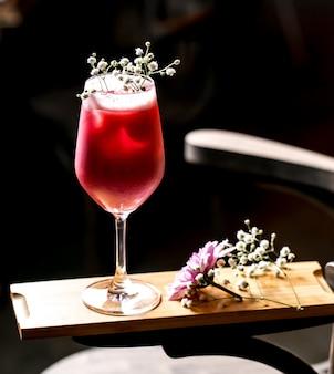 Cocktail roxo decorado com gypsophila em copo de pé longo