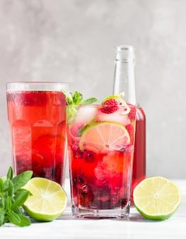 Cocktail sem álcool rosa frio com cubos de framboesa, limão, hortelã e gelo.