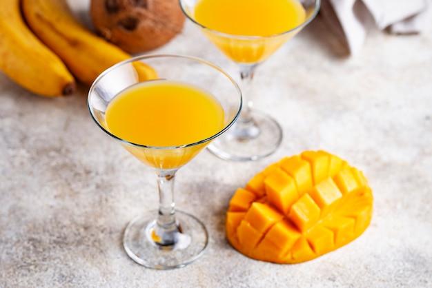 Cocktail tropical com manga em fundo claro