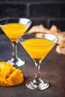 Cocktail tropical com manga em fundo escuro