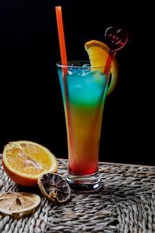 Cocktail tropical de vista lateral com túbulos para bebidas e laranja seca em servir guardanapos na mesa de madeira