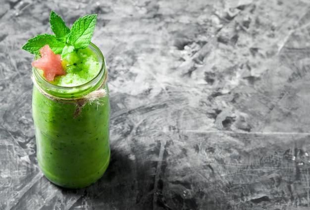 Cocktail tropical smoothie com hortelã, fatias de melancia e cubos de gelo em uma superfície de concreto cinza