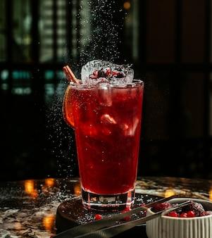 Cocktail vermelho com cubos de gelo e frutas.