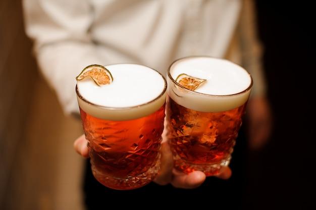 Cocktail vermelho com espuma doce e limão fresco nas mãos de barmen