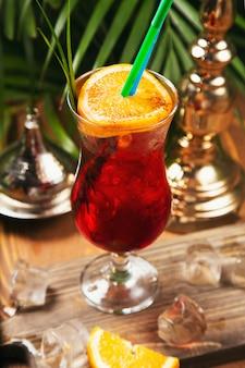 Cocktail vermelho com fatia de laranja em uma mesa de cozinha de madeira