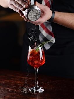 Cocktail vermelho com gelo e cereja em um copo transparente. açúcar de confeiteiro granulado em um cocktail