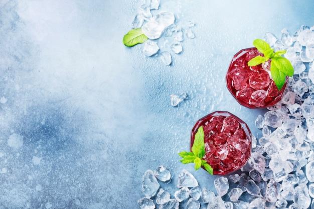 Cocktail vermelho com gelo e hortelã