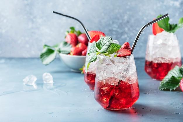 Cocktail vermelho com gelo e morango fresco