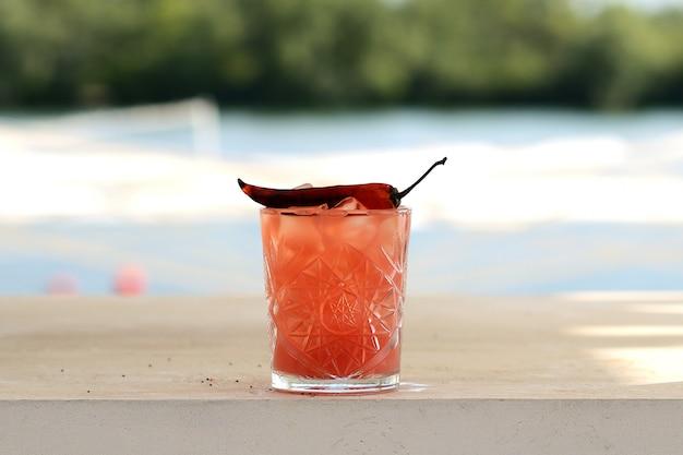 Cocktail vermelho com gelo em um copo de vidro com pimenta vermelha picante