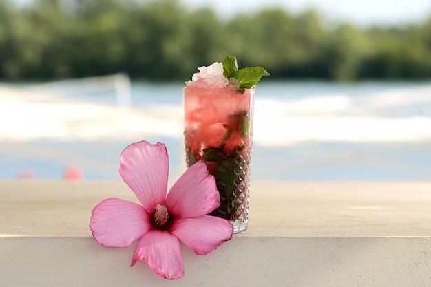 Cocktail vermelho com hortelã e gelo em uma taça de vidro. mojito com decoração de flores